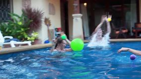 Joyful group of attractive young friends playing with a balls swimming in swimming pool. 1920x1080. Athletic group of attractive young friends playing with a stock footage