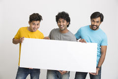 Joyful group of friends displaying white boad. Happy joyful group of friends displaying white boad for your text on white background Stock Image