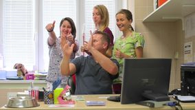 Group of people posing. Joyful group of people posing. A young man is sitting at the computer and three young women are behind him. Smiling, waving their hands stock footage