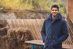 Joyful guy breathing fresh air outside. Happy young man is standing and relaxing outdoors in warm coat. He is looking at camera and smiling stock photo