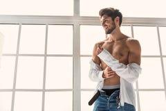 Joyful guy changing clothing at home Royalty Free Stock Photography
