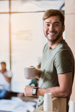 Joyful guy drinking coffee at work. Portrait of happy young men enjoying hot beverage on break. He is standing and smiling while looking at camera with joy Royalty Free Stock Image