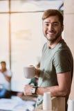 Joyful guy drinking coffee at work Royalty Free Stock Image