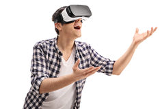 Joyful guy experiencing virtual reality. Through a VR headset isolated on white background Stock Photography