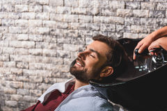 Joyful guy getting hairwash at barbershop. Happy young man is relaxing at beauty salon. He is putting head on washbasin and smiling. Hairdresser is adjusting tap Royalty Free Stock Photos