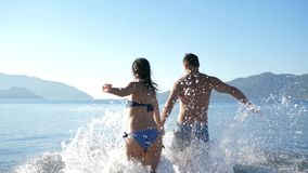 Joyful guy with girl into bikini fun spend time in water in seaside resort on holiday stock video footage
