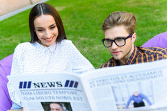 Joyful guy and girl are interested in news Stock Image