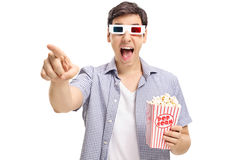 Joyful guy with a pair of 3D glasses and popcorn laughing Stock Photos