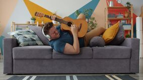 Joyful guy playing guitar singing wearing headphones having fun on sofa at home