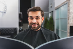 Joyful guy reading journal at hairdressers. I want this hairstyle. Cheerful young man is watching magazine with fashionable hairdos. He is looking at camera with royalty free stock photos