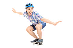 Joyful guy riding a small skateboard Stock Photos