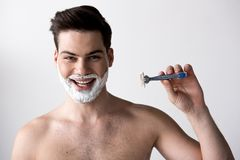 Joyful guy with shaving cream is expressing gladness. Portrait of cheerful topless man is standing and looking at camera with joy. He is holding razor while stock photos
