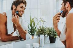 Joyful guy shaving before mirror at bathroom royalty free stock photo