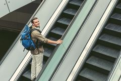 Joyful guy is standing on escalator Royalty Free Stock Photography
