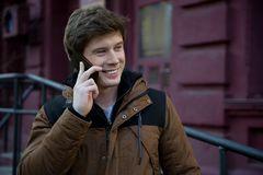 Joyful guy is standing with smartphone and calling to friends royalty free stock photo