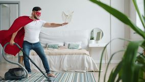 Joyful guy in superman costume cape and mask cleaning carpet with vacuum cleaner. Joyful guy in superman costume red cape and mask cleaning carpet with vacuum stock video