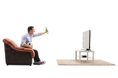 Joyful guy watching football on TV a. Nd celebrating with a beer isolated on white background Stock Photo