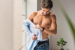 Joyful guy wearing shirt at home Stock Image