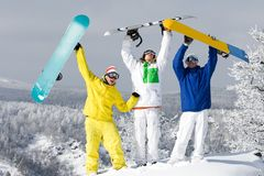 Joyful guys. Portrait of three happy young snowboarders raising their arms Royalty Free Stock Images