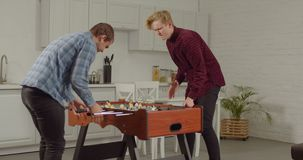 Joyful guys playing foosball in loft apartment. Excited cheerful male friends enjoying freetime playing table football in loft apartment. Positive roommates stock footage