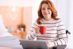 Joyful handicapped woman with her laptop and a cup Royalty Free Stock Photography