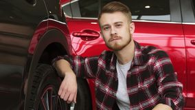Young man examining wheels and tires of a new car at the dealership royalty free stock images