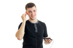 Joyful handsome guy inserts earphones into your ears and listen to music from your phone Stock Image