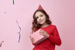 Joyful happy baby girl holds box with gift. Long wavy hair, red sweater and holiday hat on her head. Portrait on pink background. stock photos