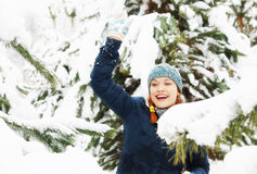 Joyful happy beautiful girl plays snowballs between snowy pine trees Stock Photography