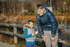 Joyful happy brother and little sister standing in autumn park and listening music trough the headphones Stock Photography