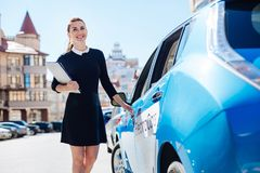 Joyful happy businesswoman holding documents. Ready to work. Joyful positive happy businesswoman holding documents and smiling while opening her car Stock Images