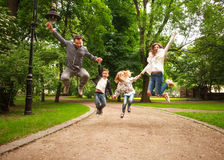 Joyful happy family in summer park together jumping have fun. Joyful happy family in summer park together jumping to have fun stock image