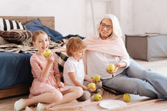 Joyful happy girl eating an apple. My favourite fruit. Joyful happy nice girl holding an apple and eating it while sitting together with her family Stock Photo
