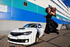 Joyful happy girl jumping near white car Royalty Free Stock Photo