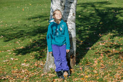 Joyful happy little girl leaning against a birch trees with closed eyes in autumn park Stock Images