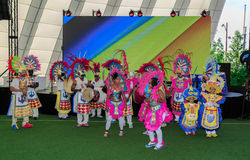 Joyful, happy people in bright colorful costumes dancing near the stage Stock Photos