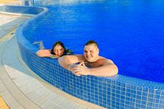 Joyful happy teenage boy and girl relaxing in swimming pool and enjoying their leisure vacation time. Smile joyful happy teenage boy and girl relaxing in Stock Images