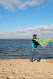 Joyful happy woman having fun, playing with a veil in the wind,. While relaxing at the coast. Beautiful autumn day Royalty Free Stock Photos