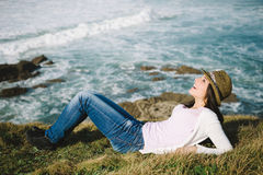 Joyful happy woman liying down towards the sea Royalty Free Stock Photography