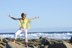 Joyful and happy woman at ocean. An attractive looking mature woman is standing on rocks, happily smiling with her arms up, enjoying the feeling of freedom and stock photos