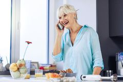 Joyful happy woman talking on the phone. Mobile communication. Joyful happy woman talking on the phone while cooking in the kitchen royalty free stock photo