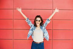 Joyful happy young woman jumping against red wall. Excited beautiful girl portrait royalty free stock images