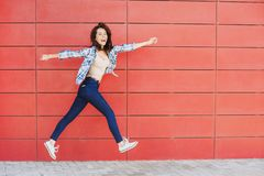 Joyful happy young woman jumping against red wall. Excited beautiful girl portrait. Joyful happy young woman jumping against red wall. Excited funny beautiful royalty free stock image