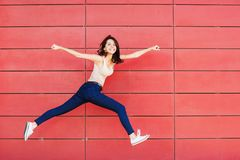 Joyful happy young woman jumping against red wall. Excited beautiful girl portrait. Joyful happy young woman jumping against red wall. Excited funny beautiful royalty free stock photos
