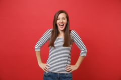 Joyful happy young woman in striped clothes keeping mouth wide open, standing with arms akimbo isolated on bright red. Wall background. People sincere emotions royalty free stock photos