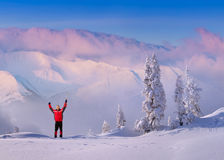 Joyful hiker meets a morning. In the snowy mountains Royalty Free Stock Image