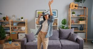 Joyful hipster having fun dancing relaxing in virtual reality glasses in house. Joyful hipster attractive young lady is having fun dancing relaxing in virtual stock video footage