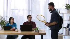 Joyful hipster entrepreneur going to play tennis stock video