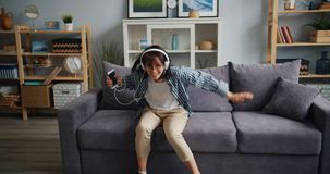 Joyful hipster in headphones having fun dancing listening to music in flat stock video footage