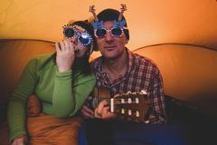 Joyful hipsters couple in travel. Men with women in the funny glasses, playing ukulele and harmonica, singing and having fun while they rest in camping royalty free stock photo